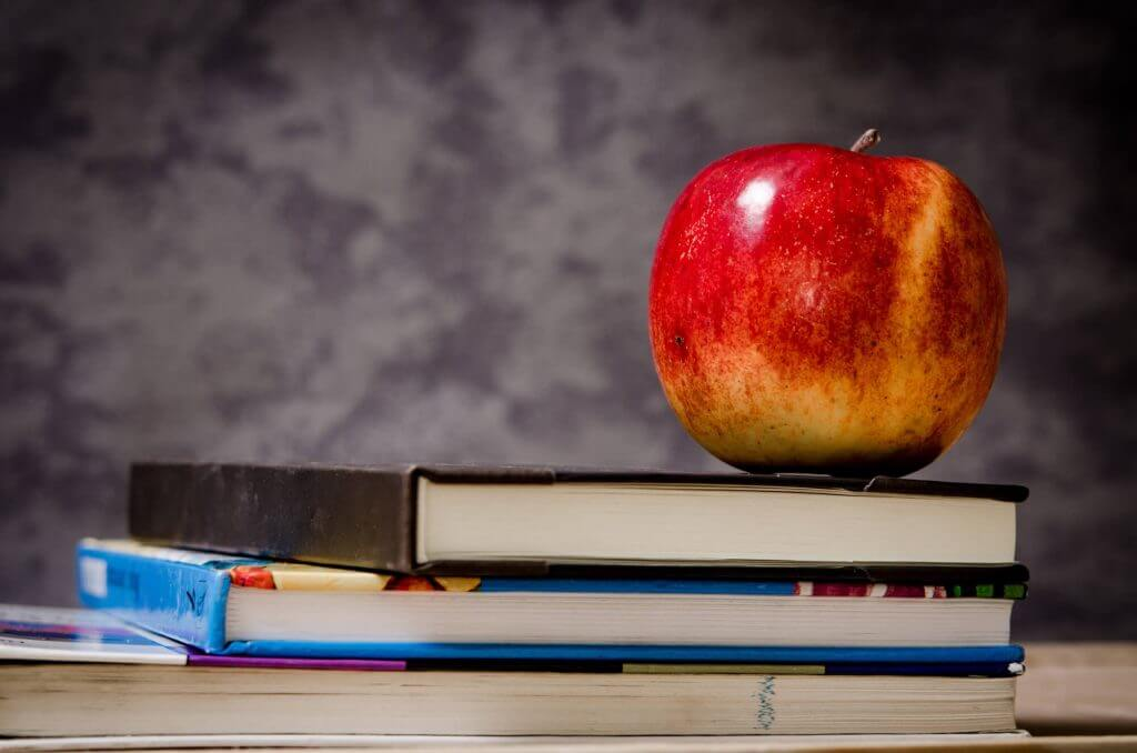 Apple sitting on top of textbooks